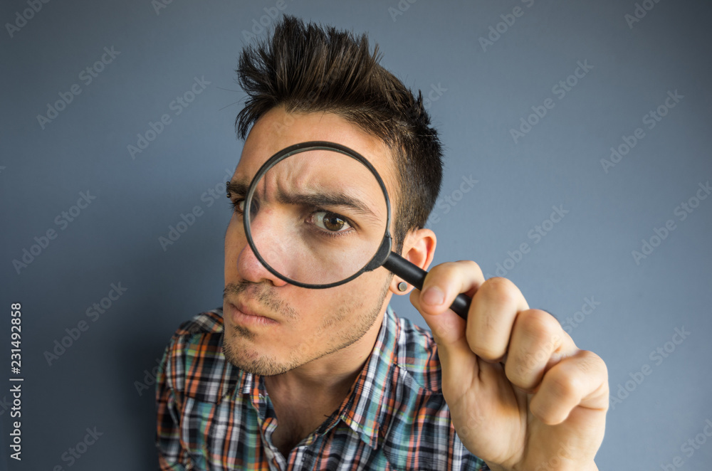 Fototapety, obrazy: Funny man of a casual man looking though magnifyng glass on a grey background