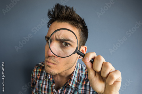 Funny man of a casual man looking though magnifyng glass on a grey background