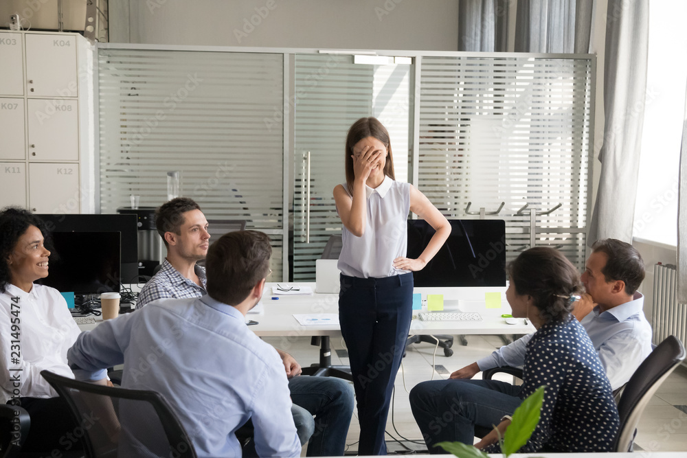 Fototapeta Shy nervous bashful female employee feels embarrassed blushing afraid of public speaking at corporate group team meeting, timid stressed woman hiding face during awkward moment reporting in office