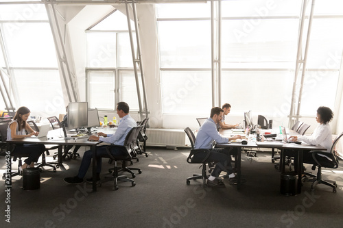 Fotografía  Diverse employees group focused on working on pc desktops in shared office room,