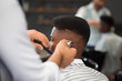 Selective focus of process of doing haircut in barber shop