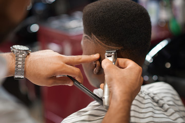 Closeup of trimming stripes on male head in barber shop