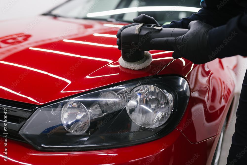 Fototapety, obrazy: Car detailing - Man with orbital polisher in repair shop polishing car. Selective focus.