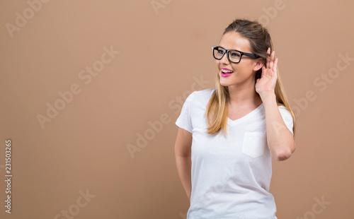Fényképezés  Young woman listening on a brown background