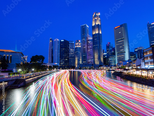 Foto op Plexiglas Donkerblauw Singapore skyscrapers and passenger boat light trails at night