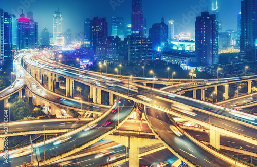 Scenic view on famous highway interchange in Shanghai, China at night. Multicolored nighttime skyline.