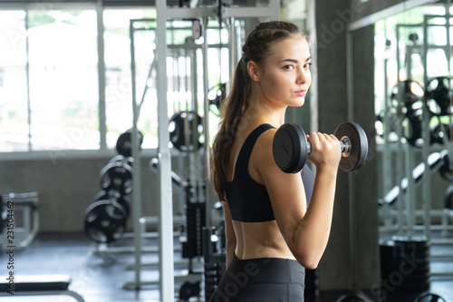 Foto op Plexiglas Fitness Muscular young woman with beautiful body doing exercises with dumbbell. Sporty girl lifting weights in gym.