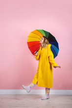 Woman With Rainbow Umbrella Near Color Wall