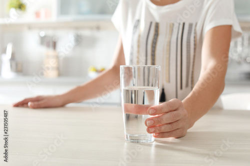 Woman holding glass with clean water on table in kitchen, closeup