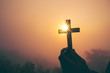canvas print picture - Silhouette of cross in human hand, the background is the sunrise., Concept for Christian, Christianity, Catholic religion, divine, heavenly, celestial or god.
