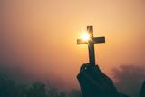 Sylwetka krzyża w ludzkiej dłoni, tło jest wschodem słońca., Koncepcja dla chrześcijaństwa, chrześcijaństwa, religii katolickiej, boskiej, niebieskiej, niebiańskiej lub boga.