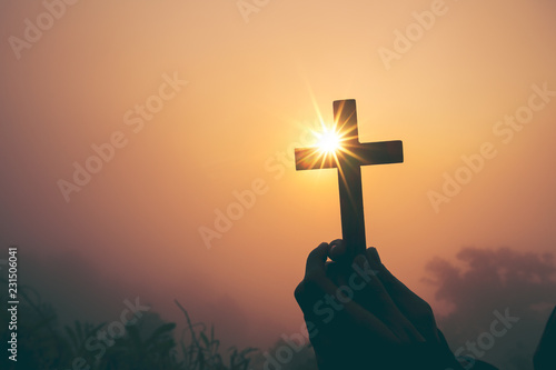 Fotografia  Silhouette of cross in human hand, the background is the sunrise