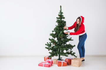 Fototapeta Winter holidays, xmas and people concept - Happy young woman dressed in santa costume decorating Christmas tree in white the room with copy space