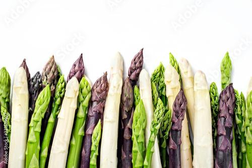 roher grüner, weißer und lila Spargel als closeup in einer Reihe mit Textfreiraum oben  – freigestellt