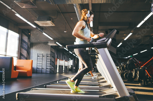 Fotografiet  Beautiful young woman with long hair trains in the gym on a treadmill