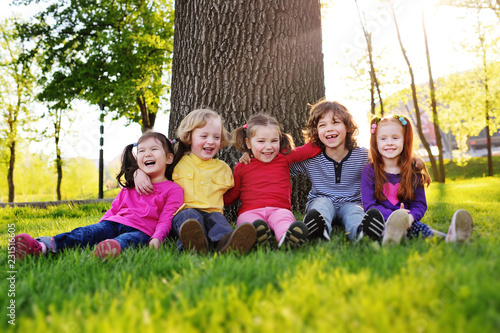 group of happy little children smiling sitting in park on grass under a tree. June 1, Children's Day, friendship, childhood, vacation.