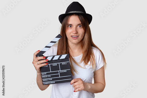 Horizontal shot of shocked beautiful young female film producer holds movie clapboard, wears hat, casual white t shirt, has stupefied facial expression. Firm director concept. Cinema industry