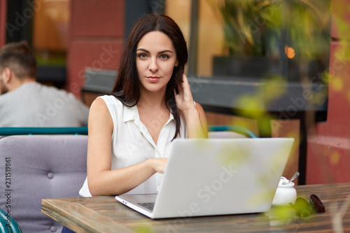 Fotografia, Obraz  Outdoor shot of beautiful brunette woman in white blouse watches educational web