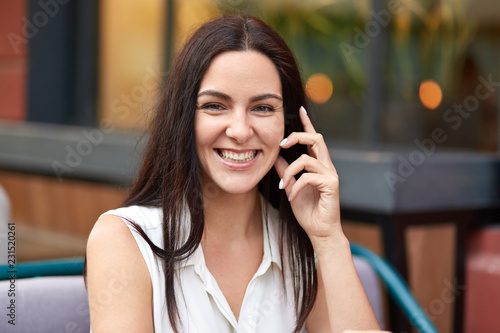 Beauty, leisure and positive emotions concept. Happy brunette young woman with toothy smile, dressed in white summer blouse, poses in outdoor coffee shop, being in good mood, enjoys day off.