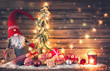 canvas print picture - Santa Claus or dwarf holds a fir tree with Christmas lights surrounded by gift boxes and glowing lantern
