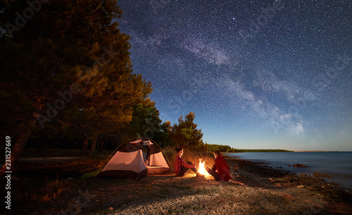 Tuinposter Kamperen Night camping on shore. Man and woman hikers having a rest in front of tent at campfire under evening sky full of stars and Milky way on blue water and forest background. Outdoor lifestyle concept