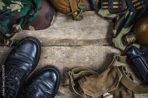 Fotografía  Army military uniform, weapon, holster, pistol, flask, boots on wooden background