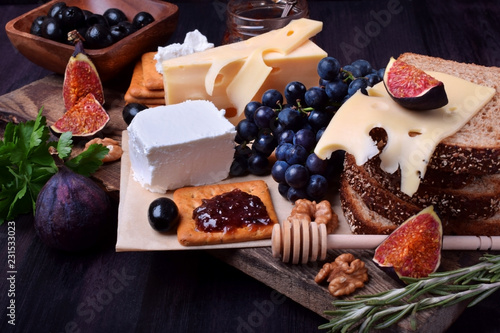 Deurstickers Voorgerecht Assortment of appetizers: different sorts of cheese, crackers, grapes, nuts, olive marmalade, figs and olives against the dark background