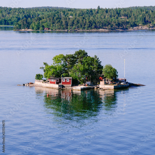 Foto auf Acrylglas Stockholm Small island in the Stockholm archipelago. Red saunas and cross waves on square frame.