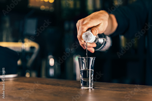Fotografia  Barmen hand with bottle pouring beverage into glass