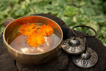 A Copper Singing Bowl Stands On A Stump Filled With Water That Floats The Healing Flowers Of Calendula. Next To Her Are The Tibetan Tingsha. Meditation Attributes Side View.