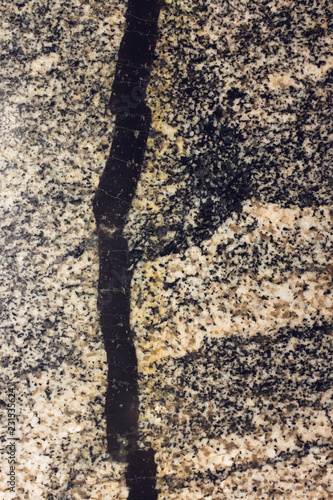 Abstract granite texture with solid black snake-like seam Wallpaper Mural