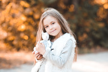 Pretty Child Girl 5-6 Year Old Holding Cute Toy Rabbit Outdoors. Looking At Camera. Childhood.
