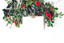 Festive Christmas Mockup Scene. Greeting Card With Golden Paper Binder Clip, Eucalyptus And Holly Red Berries, Leaves And Branches On White Table Background. Winter Wedding.