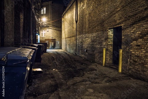 Dark and scary downtown urban city street corner alley with an eerie vintage industrial warehouse factory entrance and dirty dumpsters at night