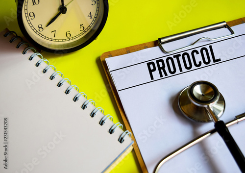 Fotografía  A stethoscope, alarm clock and notebook with word PROTOCOL on top of yellow background
