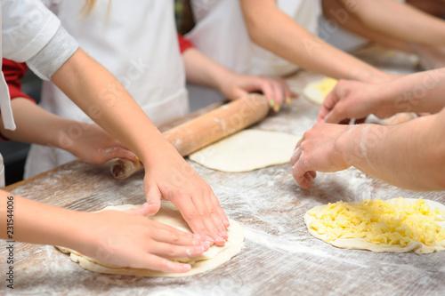 Foto op Plexiglas Koken Young children make dough products. Hands closeup