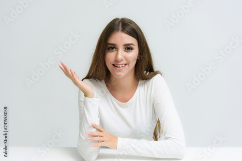 Fotografia  Studio portrait of a smiling happy beautiful brunette girl on a white background talking and sitting at the table