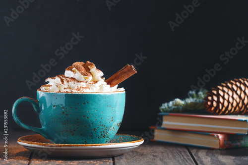 Spoed Foto op Canvas Chocolade Hot chocolate with cream and cinnamon stick in a blue ceramic cup on a table with a books. The concept of winter or fall time.