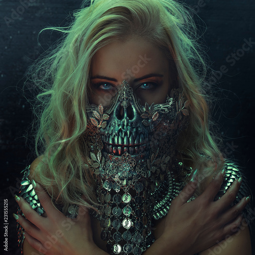 beautiful blonde woman with intense look wearing a silver mask with skull and me Fototapet