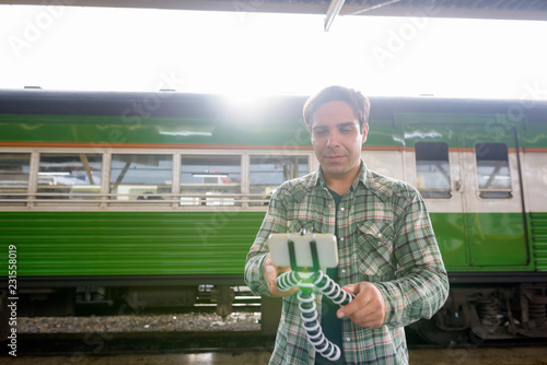 Foto  Handsome Persian tourist man at the railway station in Bangkok,
