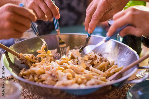 Close Up With Different Many Hands Friends Taking Italian Pasta Together With The Forks To Have