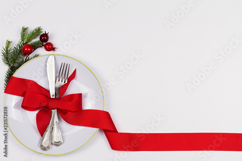 Christmas composition with plate, cutlery, pine branches, ribbon and red berries on white table. Winter holidays and festive background. Christmas eve dinner, New Year food lunch.  top view