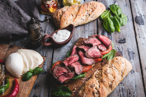 Steak sandwich, sliced roast beef, cheese,spinach leaves,tomato
