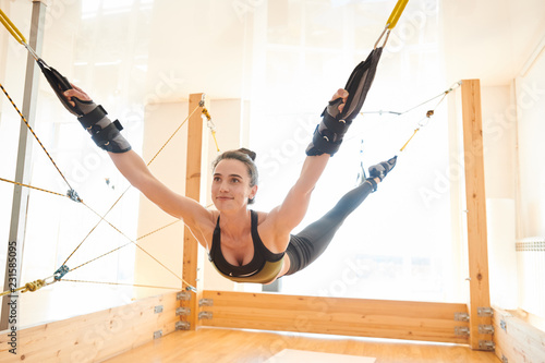 Content Satisfied Young Woman In Sports Bra And Leggings Hanging On Durable Straps Joint To Wooden Planks While She Practicing Fly Yoga In Studio Buy This Stock Photo And Explore Similar