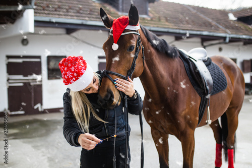 Beautiful young woman enjoying with her horse in winter holidays.