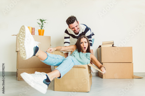 Obraz na plátně Happy couple having fun moving in the new house playing riding cardboards