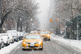 Fototapeta Nowy York - Taxis drive down a snow covered 5th Avenue during a winter nor'easter storm in New York City