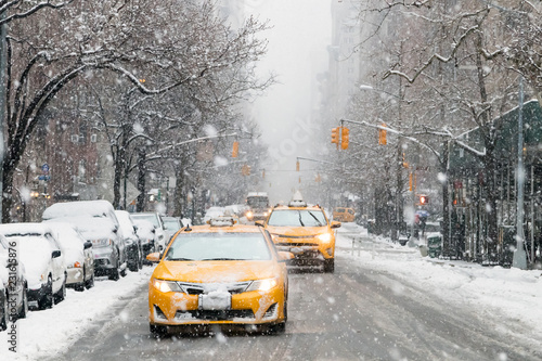 Poster New York TAXI Taxis drive down a snow covered 5th Avenue during a winter nor'easter storm in New York City