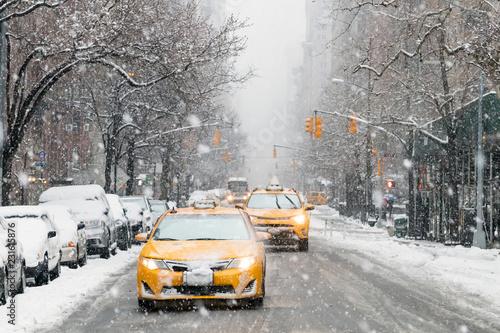Taksówki zjeżdżają 5-tą aleją pokrytą śniegiem podczas zimowej burzy nor'easter w Nowym Jorku