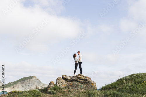 фотография Young couple walking on nordic sea coast with mountain view in spring, casual st
